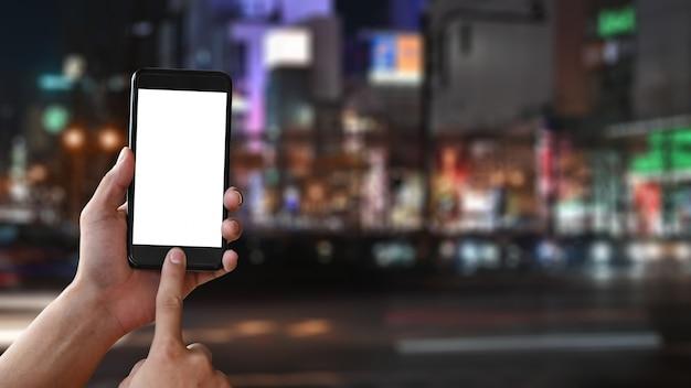 Copi le mani del primo piano dello spazio che tengono lo smartphone del modello sul fondo della sfuocatura della città di notte del giappone.