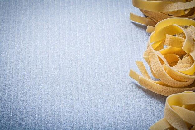 Copi lo spazio delle fettuccine della pasta rotolata sulla superficie blu
