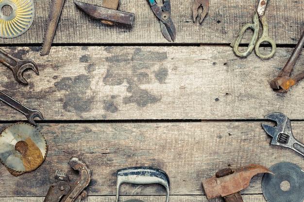 Copi lo spazio su vecchio fondo di legno con gli strumenti arrugginiti d'annata