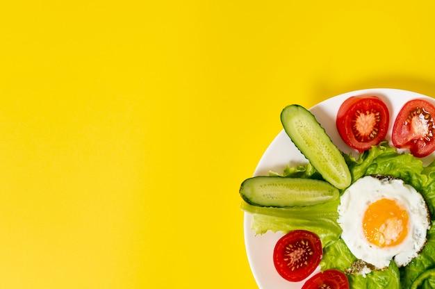Copi lo spazio uovo fritto con il piatto degli ortaggi freschi su fondo normale