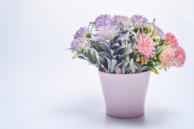 Copia spazio bellissimi fiori in un vaso su un muro bianco