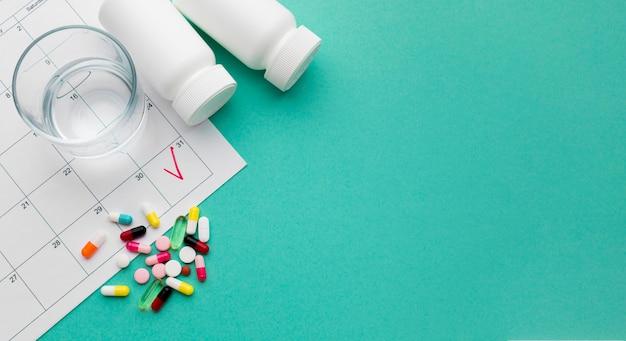 Copia-spazio bicchiere d'acqua e pillole
