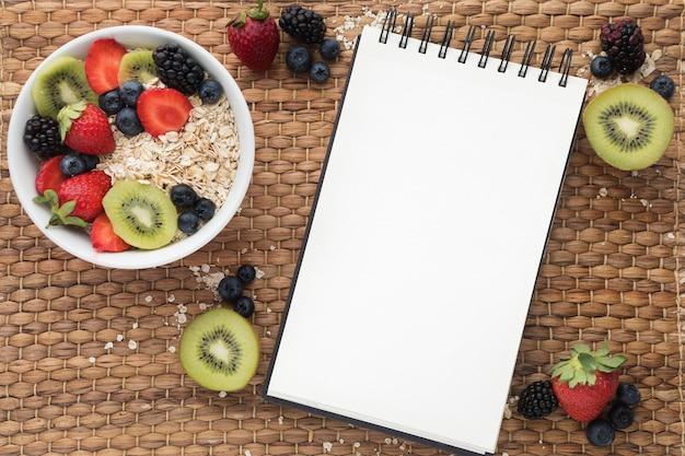 Copia spazio blocco note e cereali con frutta