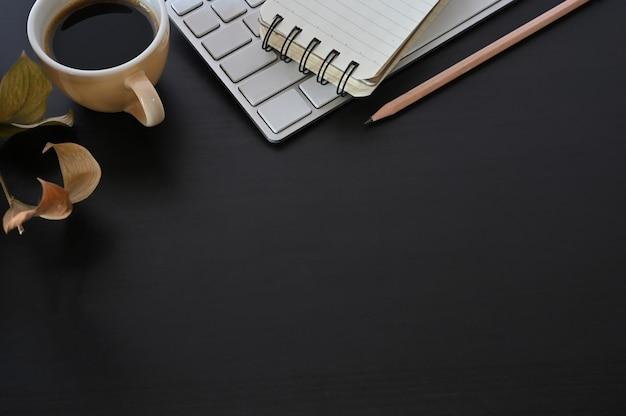 Copia spazio caffè scrivania, tastiera del computer e blocco note con la matita sul tavolo nero.