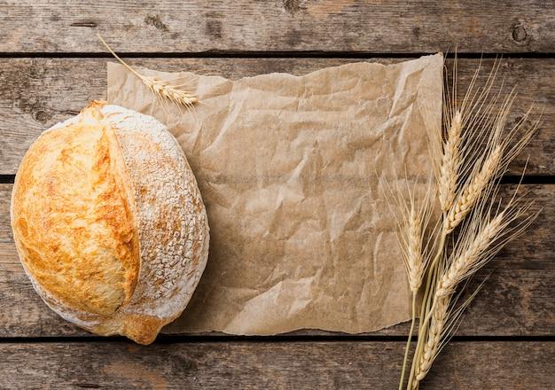 Copia spazio carta da forno con pane tondo e grano