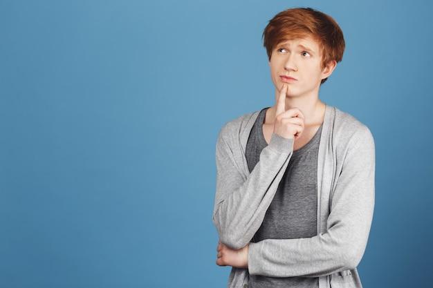 Copia spazio. colorful blue wall ritratto di giovane studente maschio bello in abito casual tenendo il dito vicino alla bocca con espressione pensierosa, pensando di saltare la lezione in università.