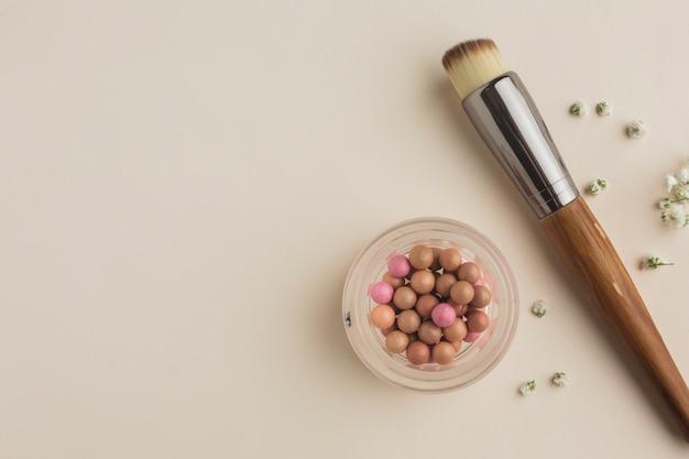 Copia-spazio con fard e pennello sul tavolo