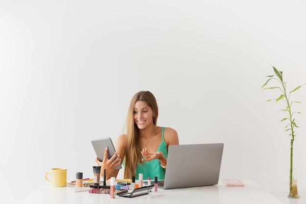 Copia-spazio femminile alla scrivania con prodotti di bellezza