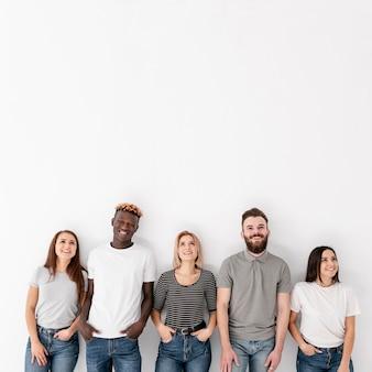 Copia-spazio gruppo di amici in piedi accanto al muro
