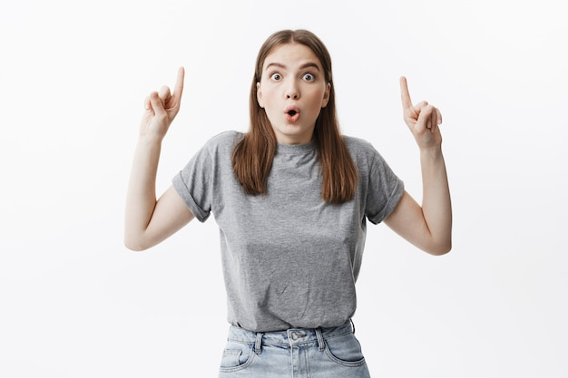 Copia spazio per pubblicità. attraente giovane donna caucasica con i capelli scuri e gli occhi schioccanti con sguardo sorpreso, rivolto verso l'alto con il dito indice sulle mani.