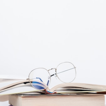 Copia-spazio pila di libri con gli occhiali