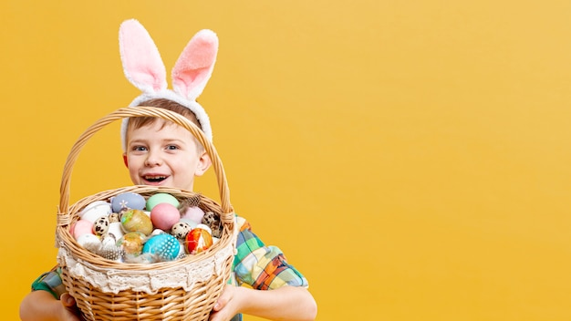 Copia-spazio ragazzo con cesto pieno di uova dipinte