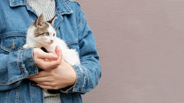 Copia-spazio simpatico gatto seduto tra le braccia del proprietario