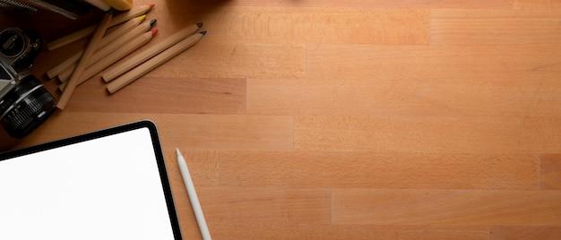 Copia spazio sulla scrivania con tablet, fotocamera, libri e articoli di cancelleria