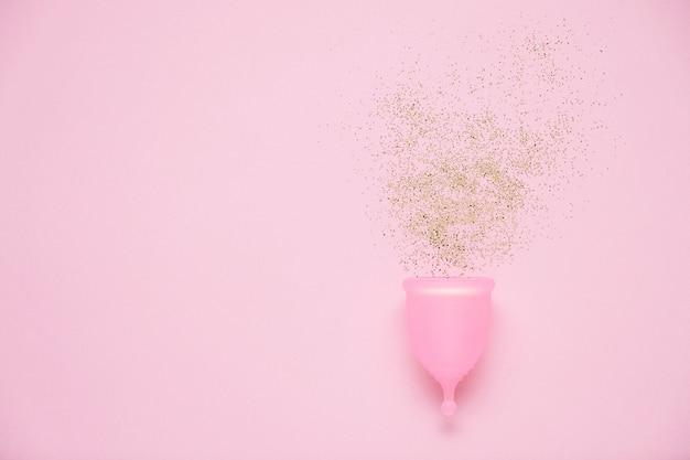 Coppa mestruale su sfondo rosa. prodotto alternativo per l'igiene femminile durante il periodo. concetto di salute delle donne