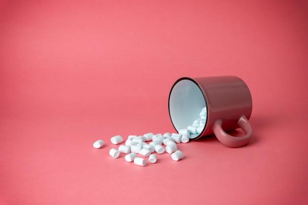 Coppa rovesciata con marshmallow su uno sfondo rosa