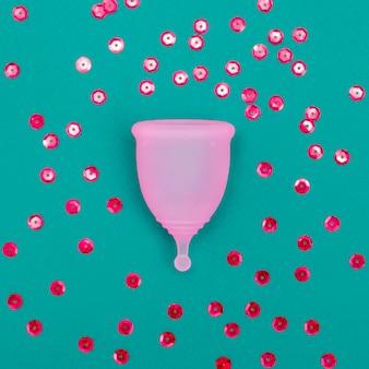 Coppetta mestruale rosa con scintillii rossi