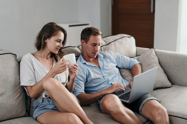 Coppia a casa loro usando il portatile insieme al mattino
