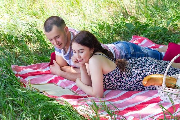 Coppia a fare un picnic. ragazzo e ragazza stanno mentendo e leggendo il libro