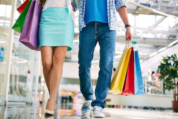 Coppia a piedi lungo centro commerciale con borse della spesa