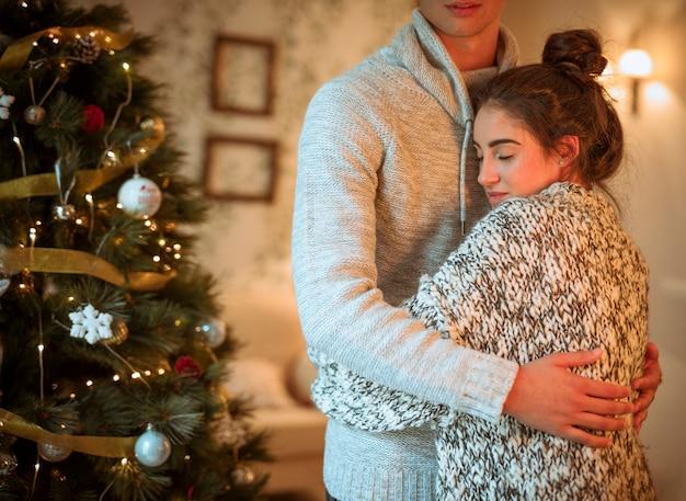 Coppia abbracciando all'albero di natale