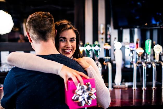 Coppia abbracciarsi in un bar dopo che l'uomo ha dato un regalo alla sua ragazza