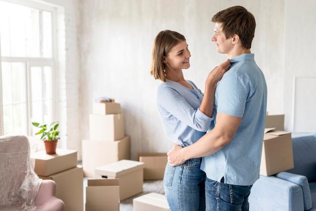 Coppia abbracciata a casa mentre fa le valigie per cambiare casa