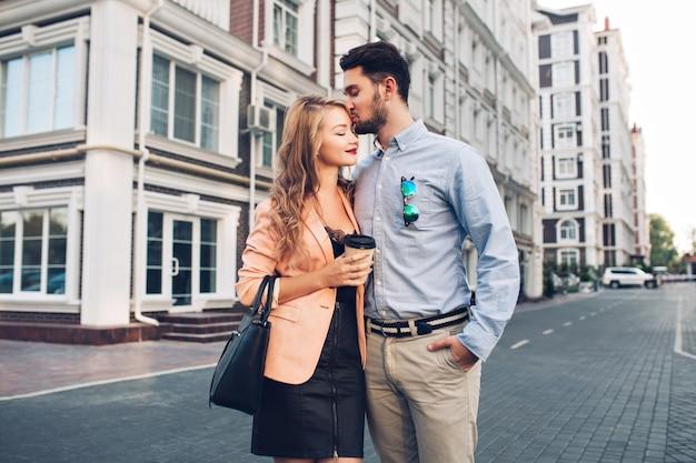 Coppia adorabile in giro per il quartiere britannico. uomo dai capelli scuri in camicia blu che bacia in testa ragazza bionda in abito nero con giacca di corallo.