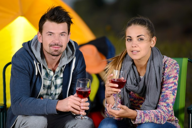 Coppia affascinante vicino a un fuoco mentre in campeggio bere vino.