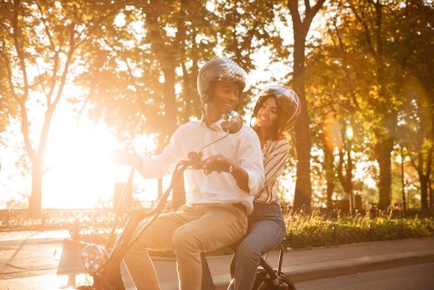 Coppia africana spensierata cavalca su una moderna moto nel parco e guardando l'un l'altro