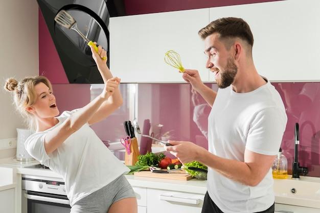Coppia al chiuso scherzando in cucina con oggetti