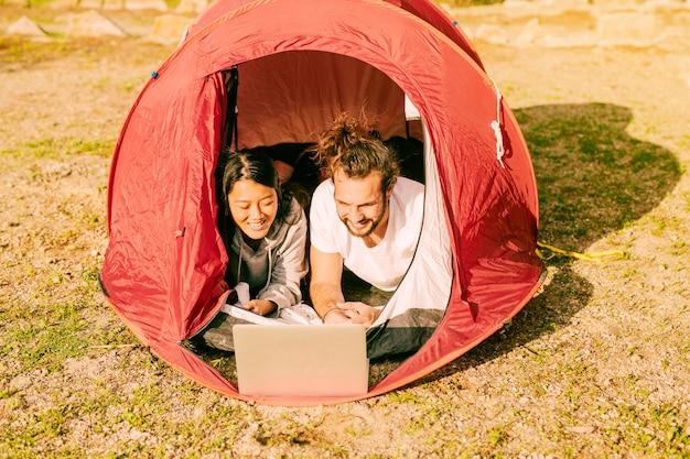 Coppia alla moda che giace in tenda con il portatile