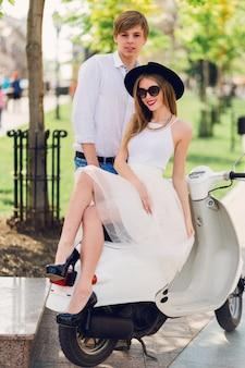 Coppia alla moda in posa per strada, posa su scooter, indossando abiti casual alla moda