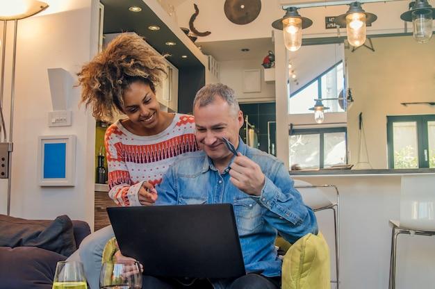Coppia allegra guardando il computer mentre si distende sul divano, l'uomo in possesso di una carta di credito - acquisti online, persone che acquistano un nuovo regalo dal sito web di e-commerce