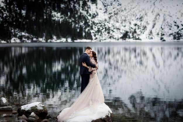 Coppia appena sposata che bacia sul paesaggio delle montagne