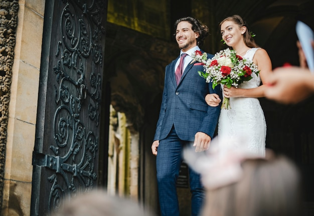 Coppia appena sposata che cammina fuori dalla chiesa