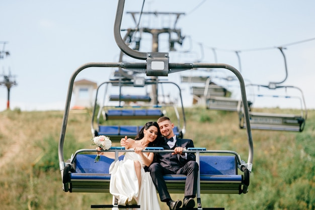 Coppia appena sposata che guida giù dalla montagna in funivia in estate. ritratto di sposi felici in teleferica. grom con la sposa celebra il giorno della sposa. bella coppia amorevole che gode del matrimonio.
