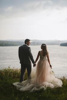 Coppia appena sposata in piedi in natura tenendosi per mano e guardando bella vista sul fiume. godendo in ogni momento nel loro giorno speciale.
