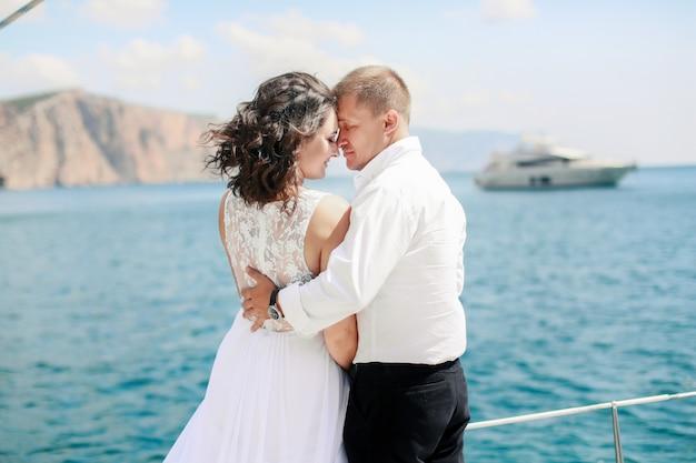 Coppia appena sposata su yacht. sposi felici il giorno delle nozze
