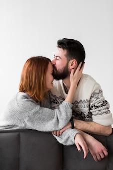Coppia appoggiata sul divano e baciare