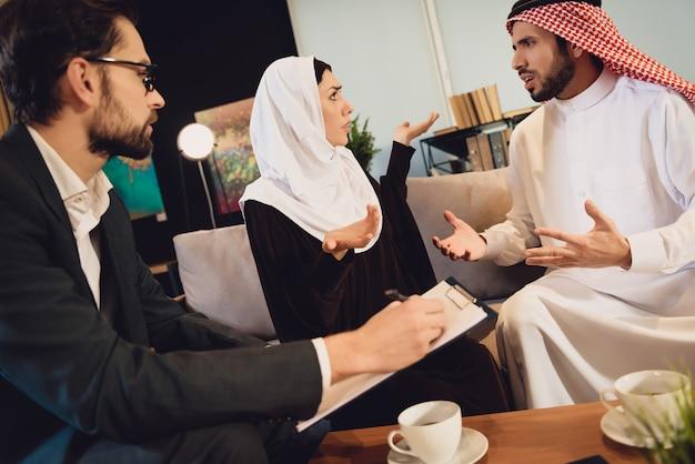 Coppia araba alla reception con un terapeuta che discute.