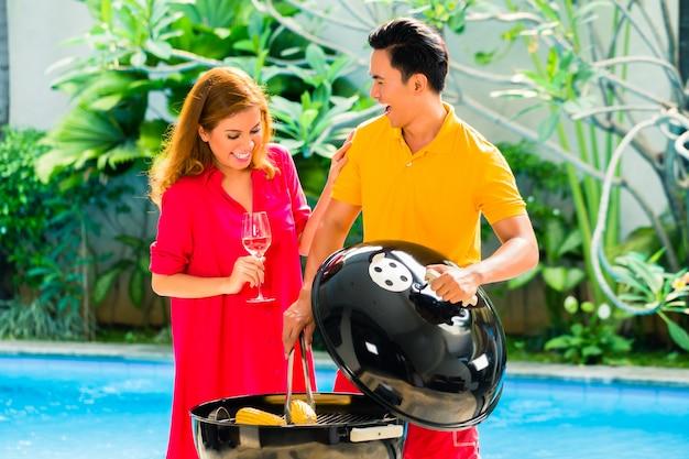 Coppia asiatica con barbecue in piscina