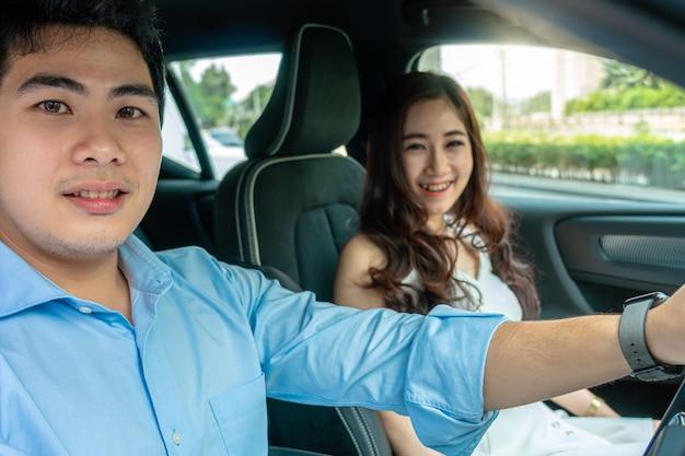 Coppia asiatica sta guidando in auto per test drive prima di acquistare una nuova auto