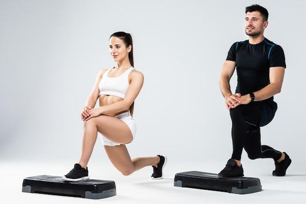 Coppia atletica facendo esercizi su passaggi in classe aerobica isolati su sfondo bianco