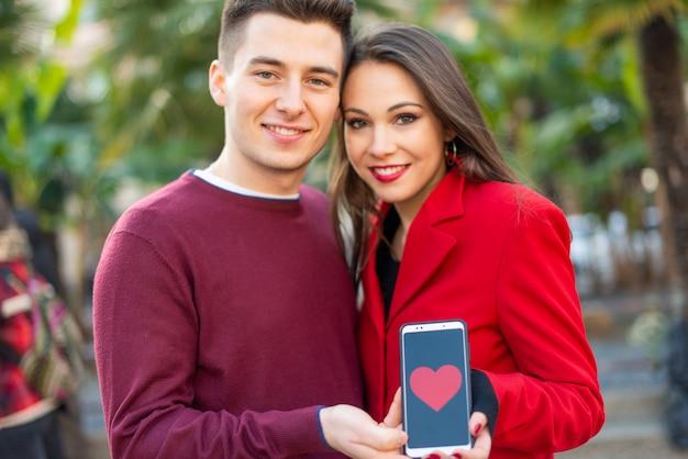Coppia baciare mentre mostrano uno smartphone con una forma del cuore, datando il concetto dell'applicazione