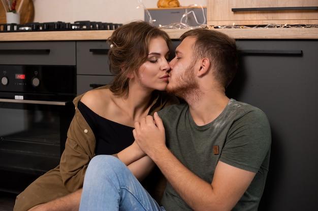 Coppia baciarsi in cucina seduto sul pavimento