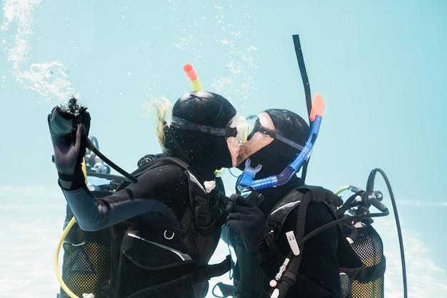 Coppia baciarsi sott'acqua durante le immersioni subacquee