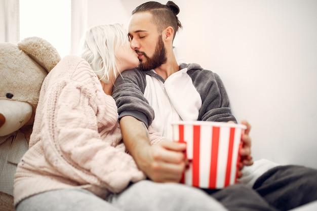 Coppia baciarsi su un letto con una ciotola di popcorn