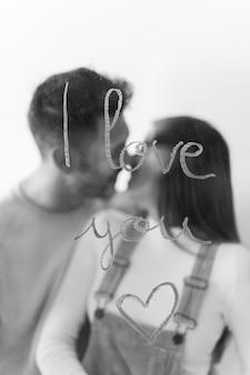 Coppia baciarsi vicino ti amo iscrizione su vetro