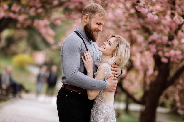 Coppia bella, allegra e carina in fiore di ciliegio in fiore rosa, giardino di sakura, abbracci e guardando l'un l'altro in una giornata di sole. ritratto di matrimonio di primavera